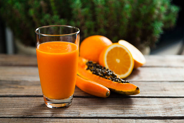Orange, papaya and carrot smoothie Healthy orange, papaya and carrot smoothie papaya smoothie stock pictures, royalty-free photos & images
