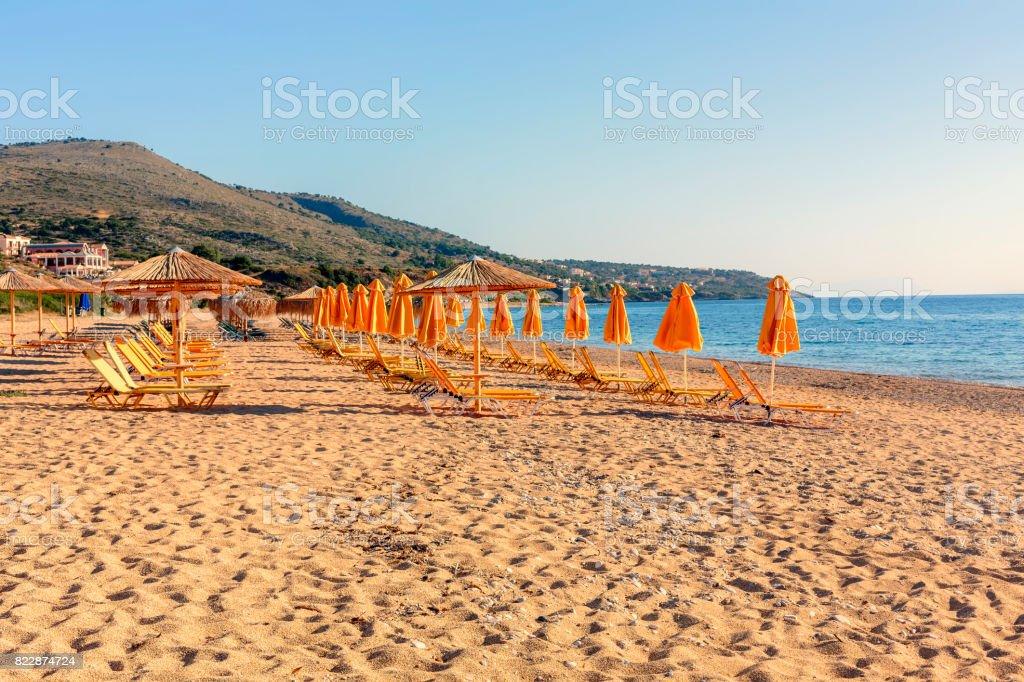 Orange parasols at Skala beach in Kefalonia at sunrise stock photo