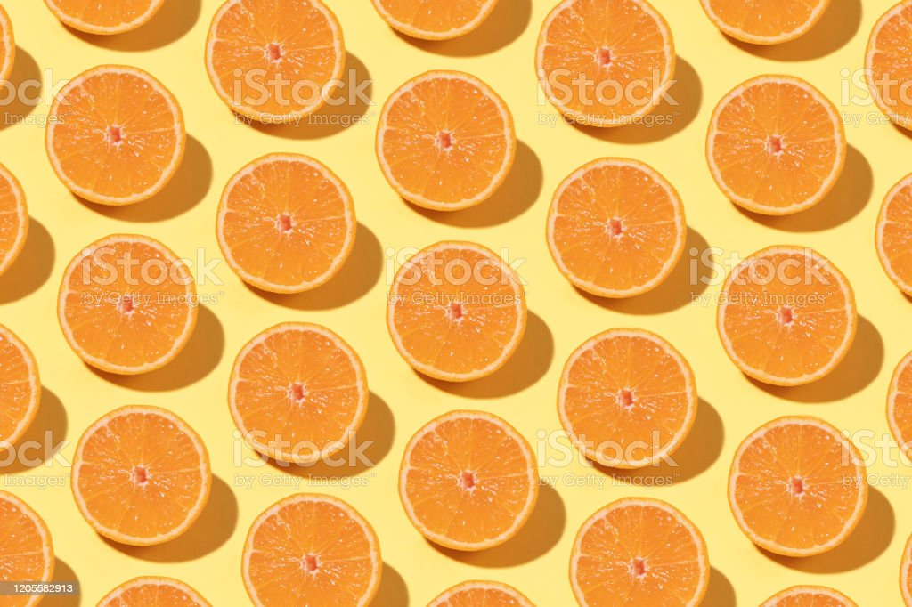 Orange Pattern on Yellow Background Fruit pattern with half slices of orange  on pastel background Abstract Stock Photo