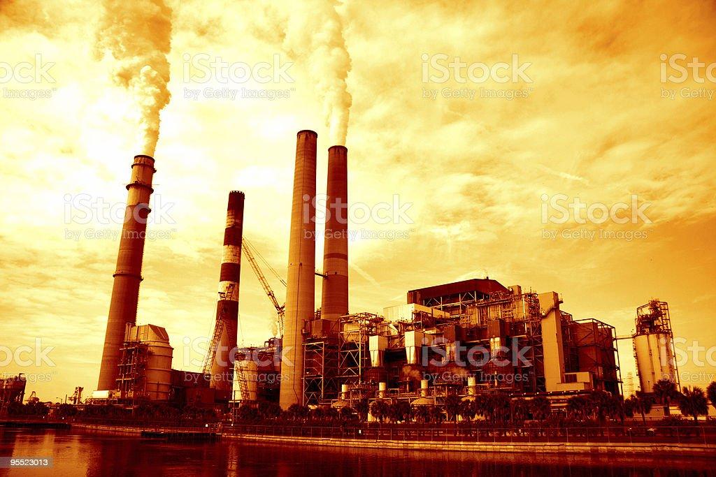 Orange photo of an industrial plant producing smoke stock photo