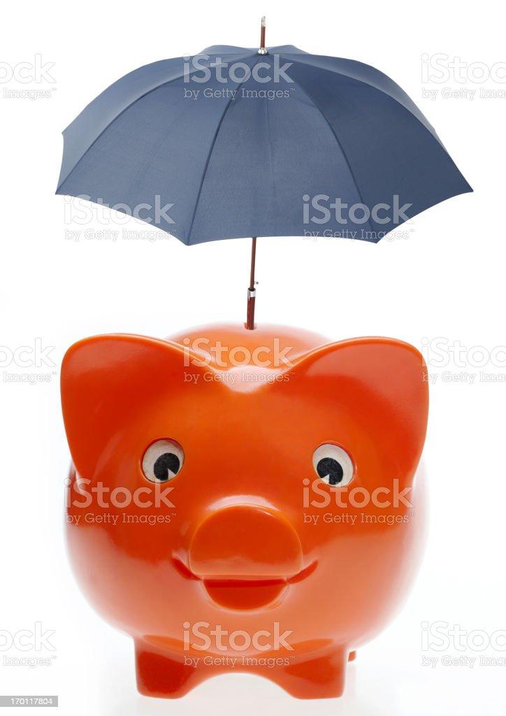 Orange Piggybank with blue umbrella on top stock photo