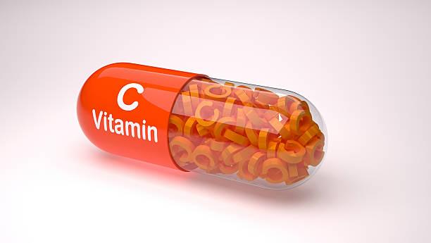 orange pill or capsule filled with vitamin c. - vitamine c stockfoto's en -beelden