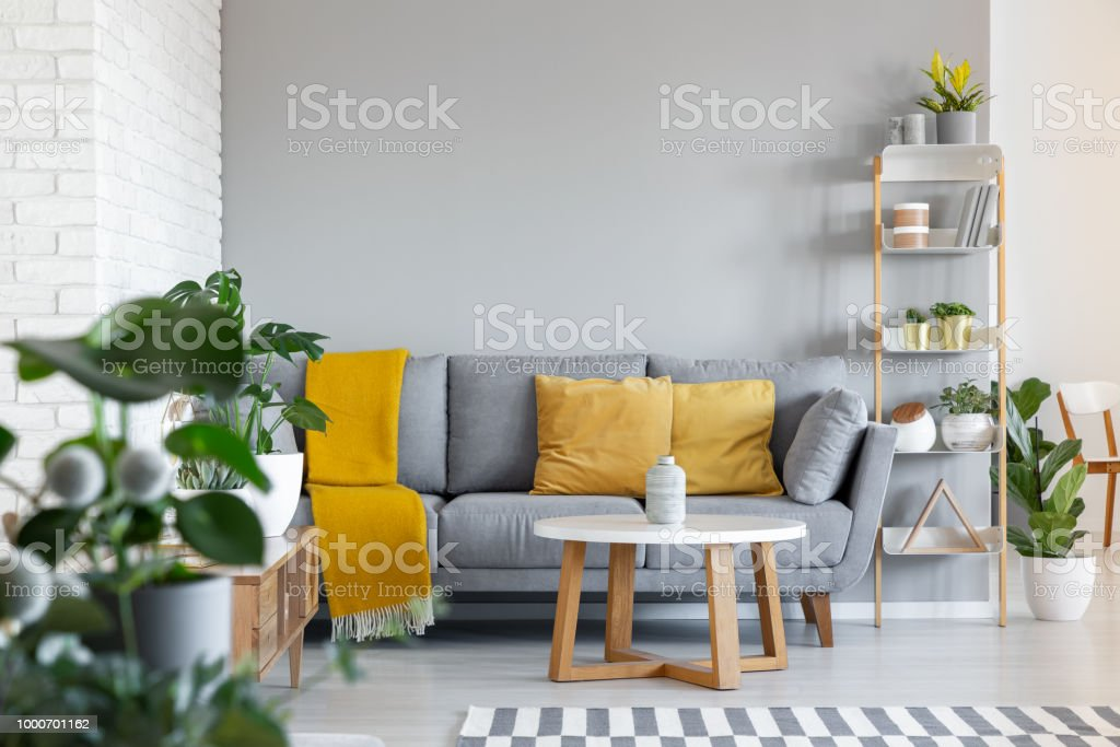 Orange pillows and blanket on grey couch in living room interior with wooden table. Real photo stock photo
