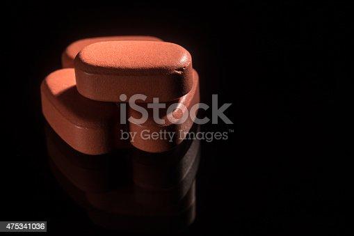 istock Orange pills on a black background 475341036