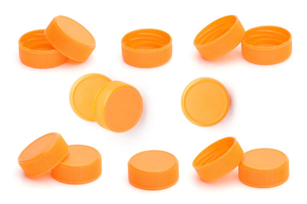 orange plastic bottle cap on white background - plastic cap stock photos and pictures