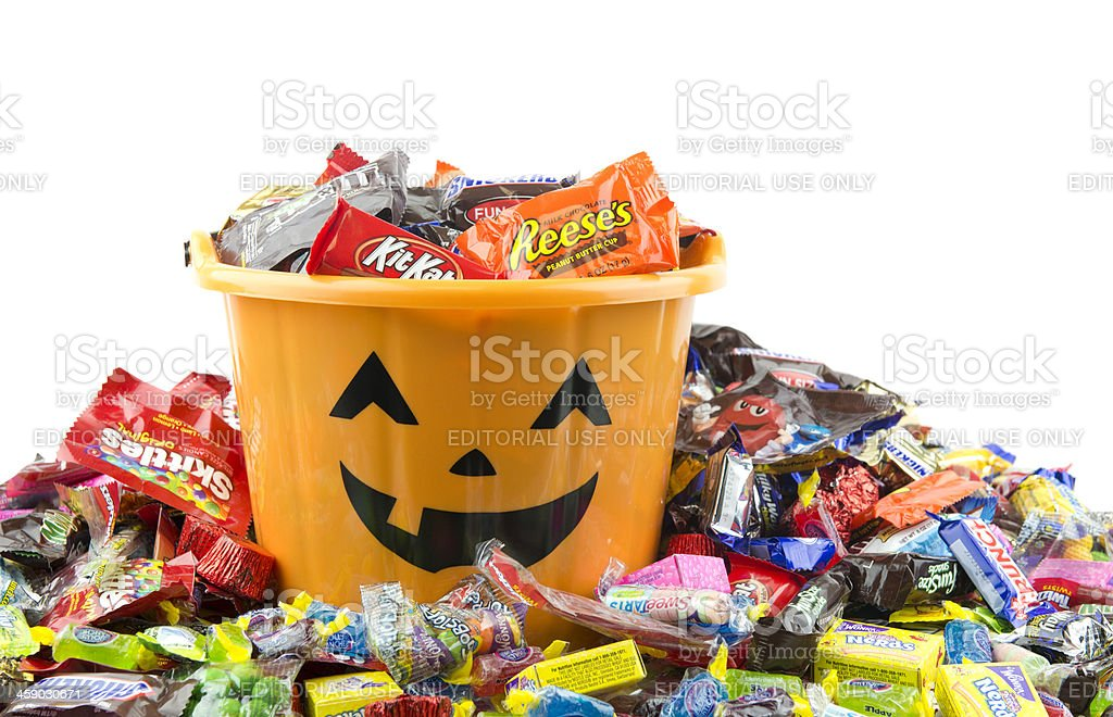 Orange plastic halloween bucket filled and overflowing with candy stock photo