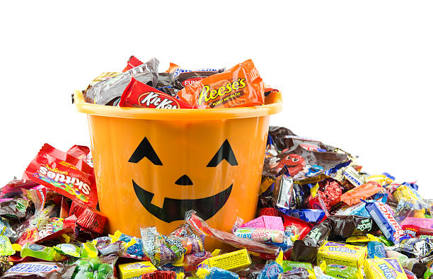 orange plastic halloween bucket filled and overflowing with candy - candy stock pictures, royalty-free photos & images