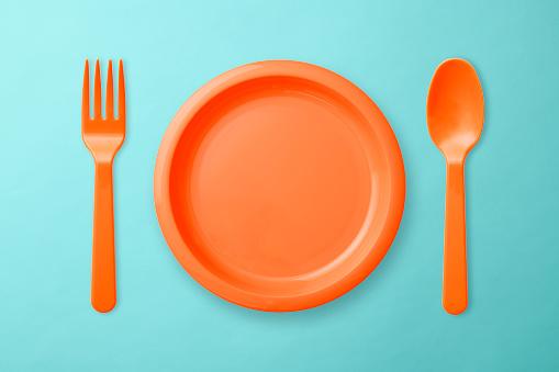 Overhead shot of orange plastic plate, Folk, and spoon on blue background.