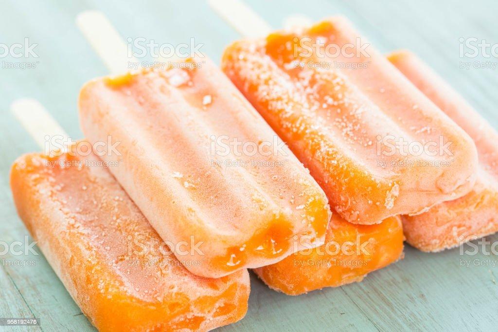 Orange Popsicles Stacked on Blue Wood Background stock photo