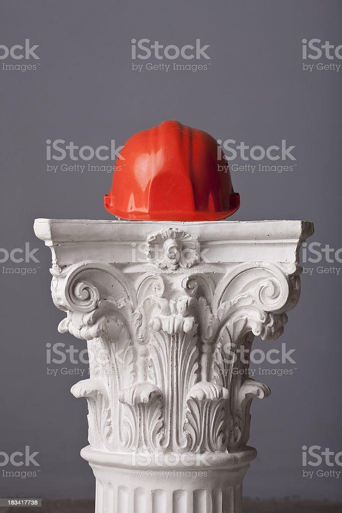 orange protection helmet on a corinthian capital royalty-free stock photo
