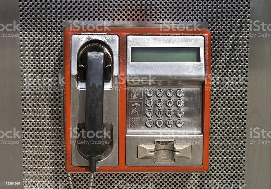 Orange public telephone on metallic background royalty-free stock photo