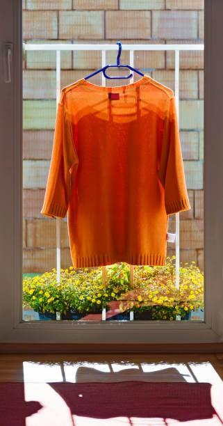 orangen pullover an einem geländer - orangenscheiben trocknen stock-fotos und bilder