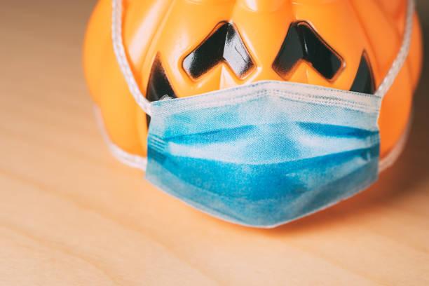 calabaza naranja con una máscara médica protectora. - halloween covid fotografías e imágenes de stock