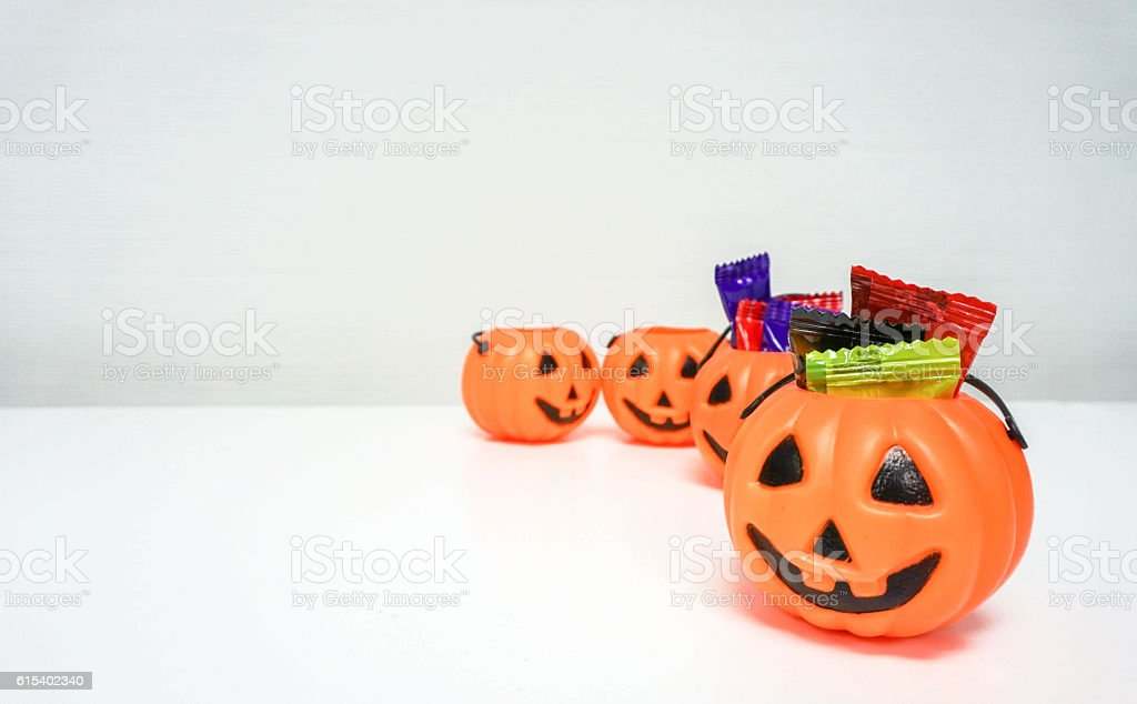 Orange pumpkin with colorful candies for Halloween party stock photo