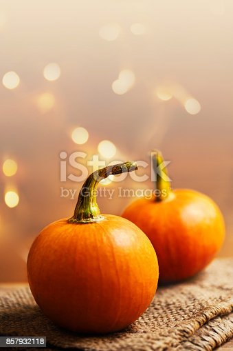 istock Orange pumpkins over wooden table. Happy Thanksgiving Day background  - rustic autumn still life with pumpkins with copy space and bokeh abstract lights