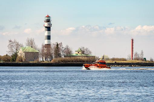 Orange rescue tug entering port of Riga town in Latvia
