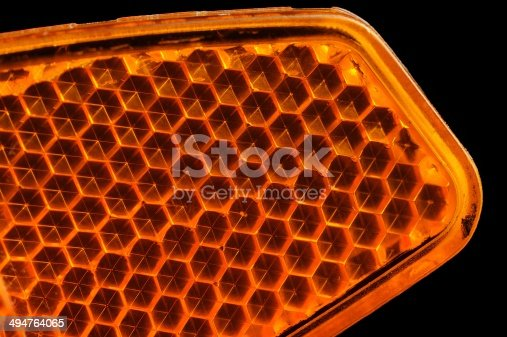 A macro shot of an orange bicycle retroreflector against a dark background