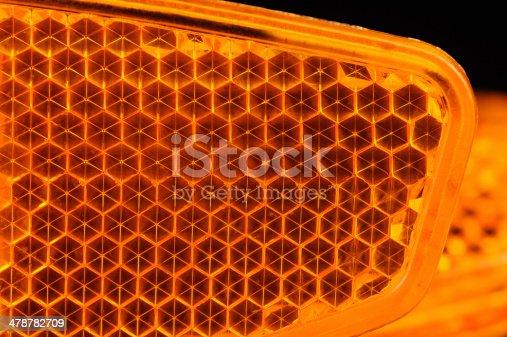 A macro shot of an orange bicycle retroreflector