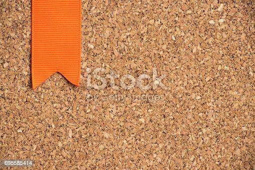 istock Orange ribbon on cork board texture background 695585414