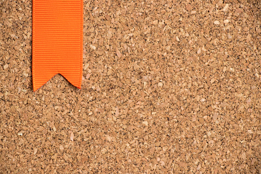 istock Orange ribbon on cork board texture background 695585414