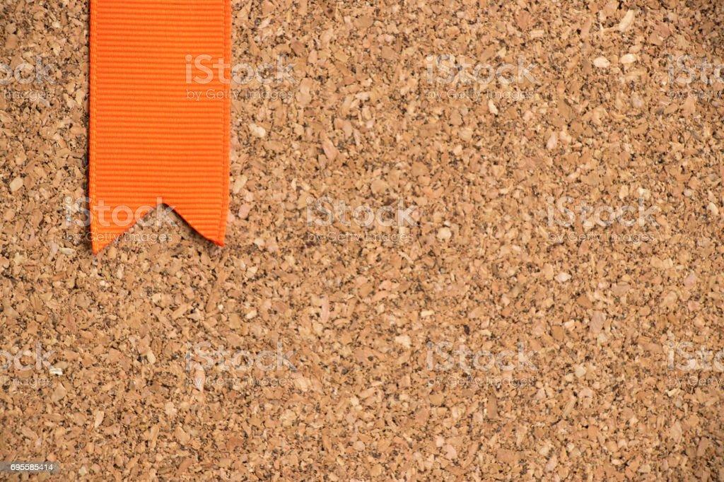 Orange ribbon on cork board texture background stock photo