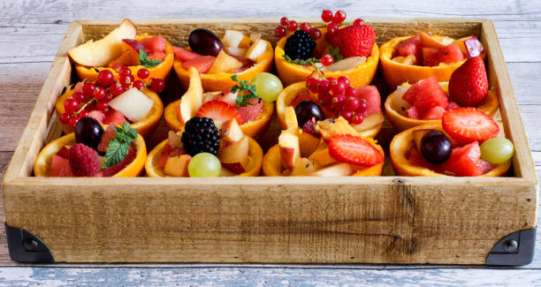 orange rinds full of fruit and berries - spieltag vorspeisen stock-fotos und bilder