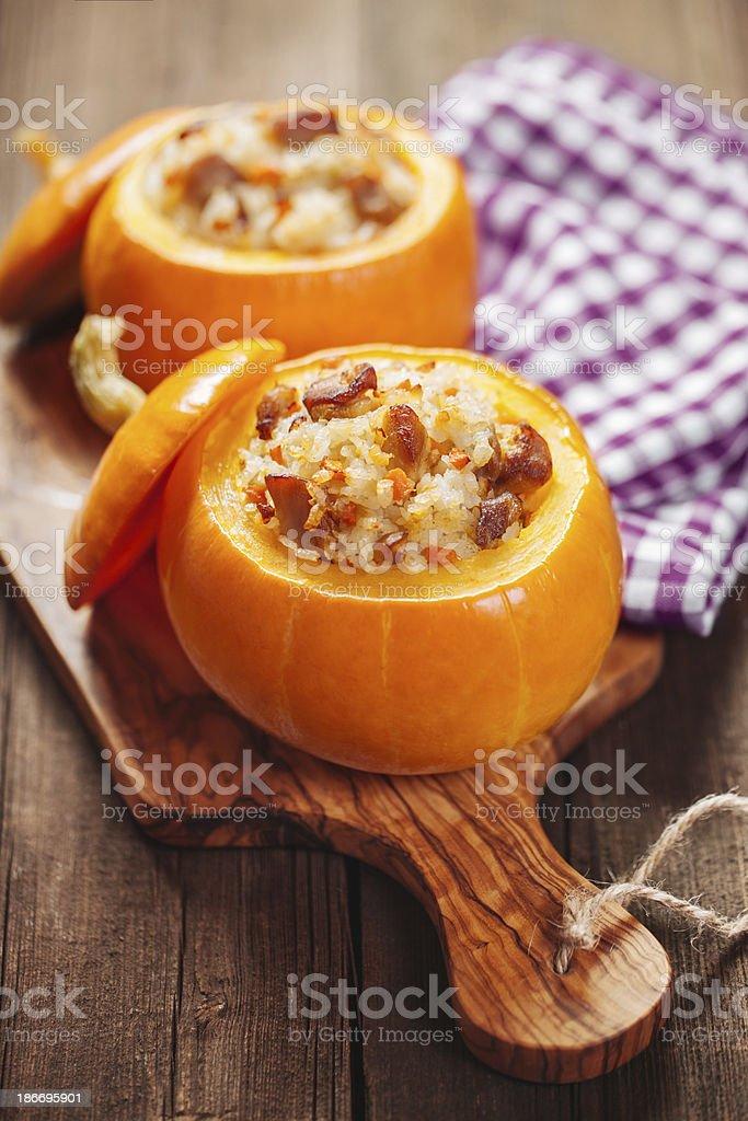 2 orange roasted & stuffed pumpkins on a wooden board stock photo
