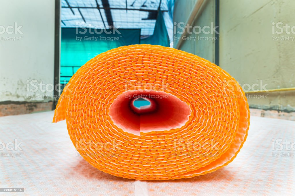 Orange roll of membrane waterproofing, separation and steam escape.  Drainage system for floor of terrace - roof, with fiber fabric. The sheath roll is resting on rolls already laid stock photo