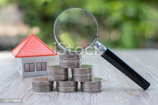 Orange roof house A magnifying glass placed on a pile of coins Concept of a businessman searching for a house Real estate investment, mortgage investment, space for entering text.