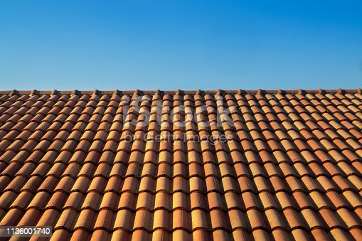 orange roof tile house against blue sky and warm sunlight at the summer time. housing and real estate concept.