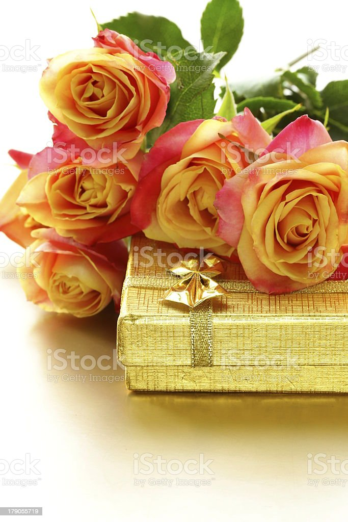 orange roses and box with gifts on gold background royalty-free stock photo
