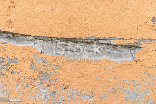 orange rough stucco on the wall with chips and cracks