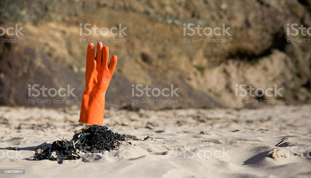 Orange rubber-glove on the beach pointing upwards from the sand stock photo