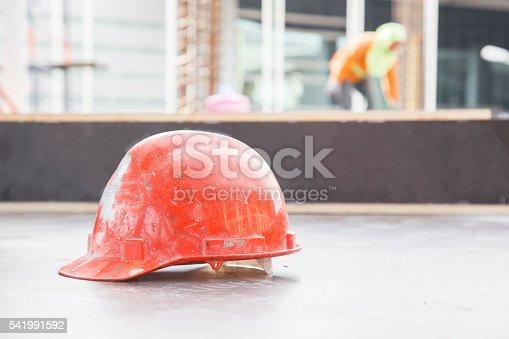 istock Orange safety helmet in construction with worker background. 541991592