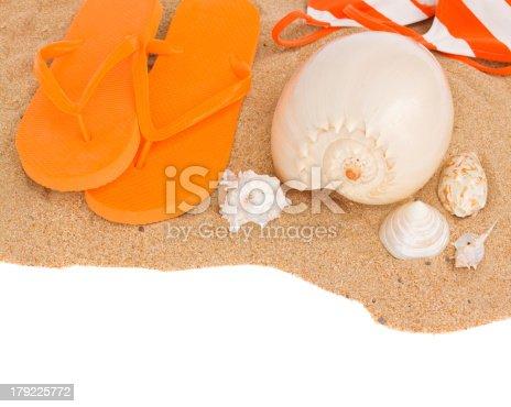 istock orange sandals and seashells on sand 179225772