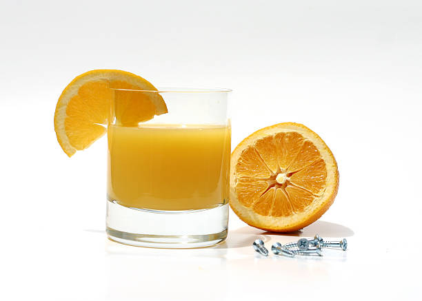 "Orange Screwdriver Photo of a alcoholic drink known as a ""screwdriver"" consist of orange juice and vodka.  This ""screwdriver"" is next to half an orange and a handfull of metal screws. screwdriver drink stock pictures, royalty-free photos & images"