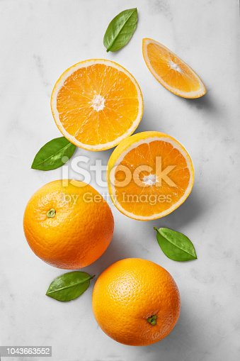 Orange selection isolated on a marble background viewed from above. Fresh citrus fruits arranged, cut and whole. Top view