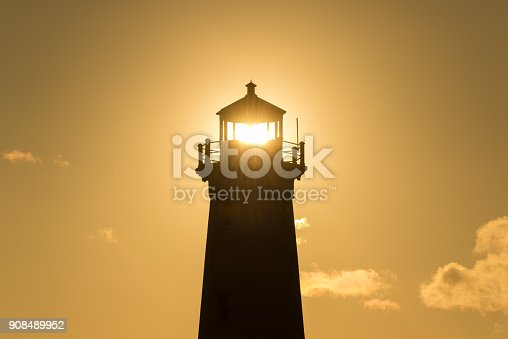 A lighthouse is silhouetted against an orange sky at sunset.