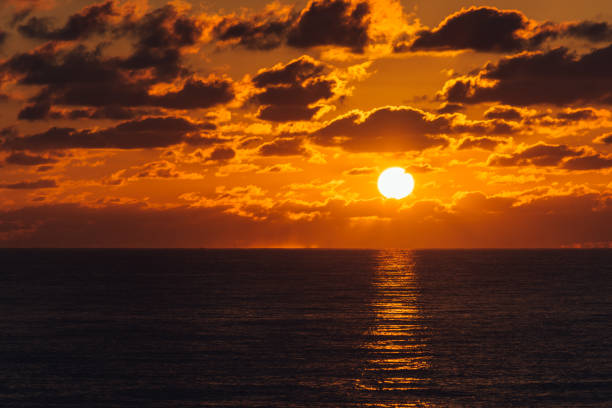 orange sky as glowing sun rises over the ocean stock photo