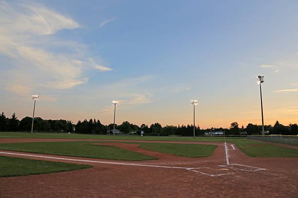 Orange Sky Ball Field A wide angle shot of a baseball field. baseball diamond stock pictures, royalty-free photos & images