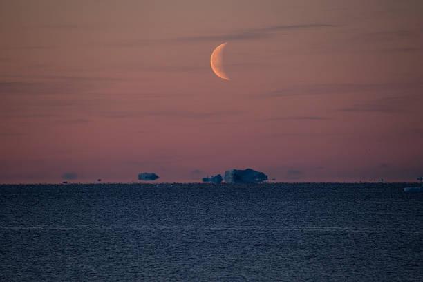 Orange sky with Half-moon over Icebergs floating near horizon stock photo