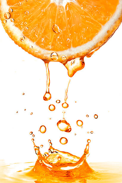 orange slice and splash of juice isolated on white - juicy stock photos and pictures