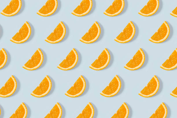 Orange Slice Pattern on Blue Background Orange slices seamless background on blue background orange fruit stock pictures, royalty-free photos & images