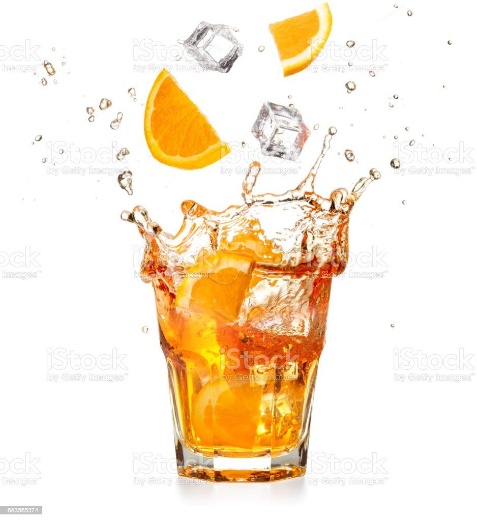 Orangenscheiben und Eiswürfel fallen in einen Spritzer cocktail – Foto