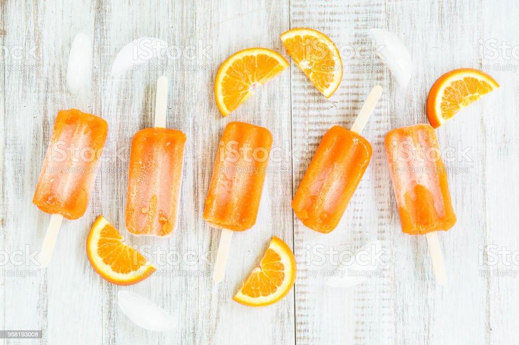 Orange Slices and Popsicles on White Wood Background stock photo