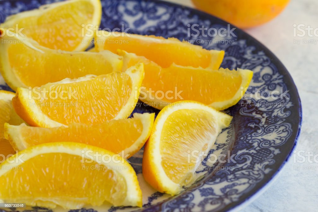 Orange slices close up on blue and white plate