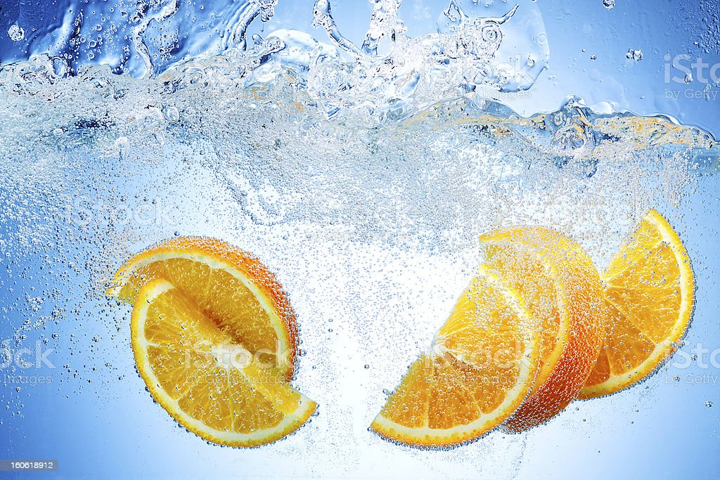 Orange Slices falling deeply under water with a big splash royalty-free stock photo