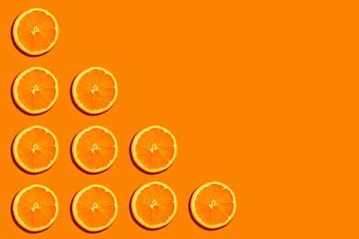 Orange slices making a triangle shape in angle of orange background