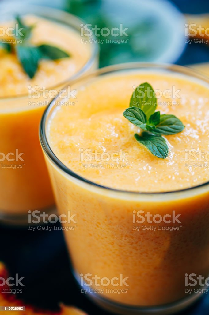 Orange smoothie with leaves of fresh mint stock photo