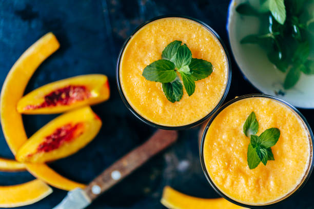 Orange smoothie with leaves of fresh mint From above view of two glass orange smoothie with leaves of fresh mint papaya smoothie stock pictures, royalty-free photos & images
